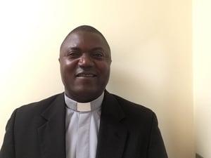 Fr-Andre-Kazadi-smiles-at-camera