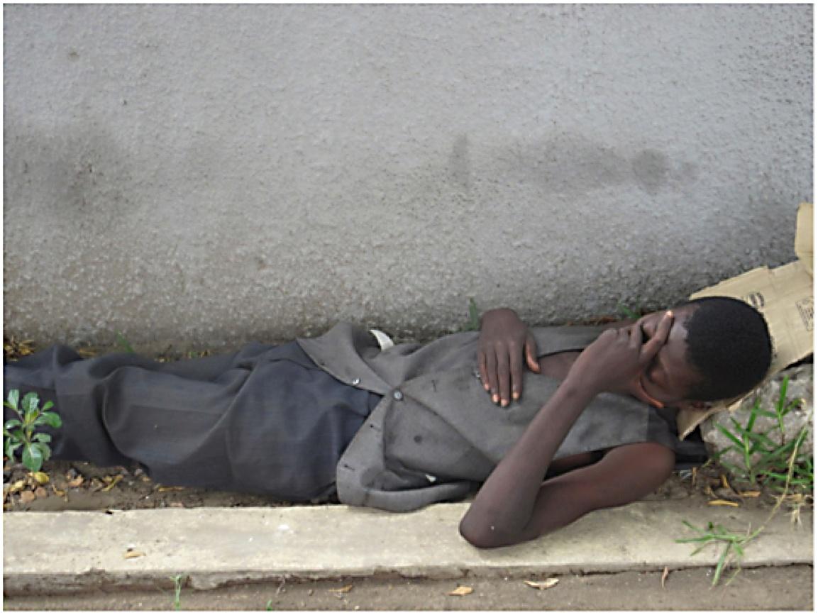 man sleeping near rock