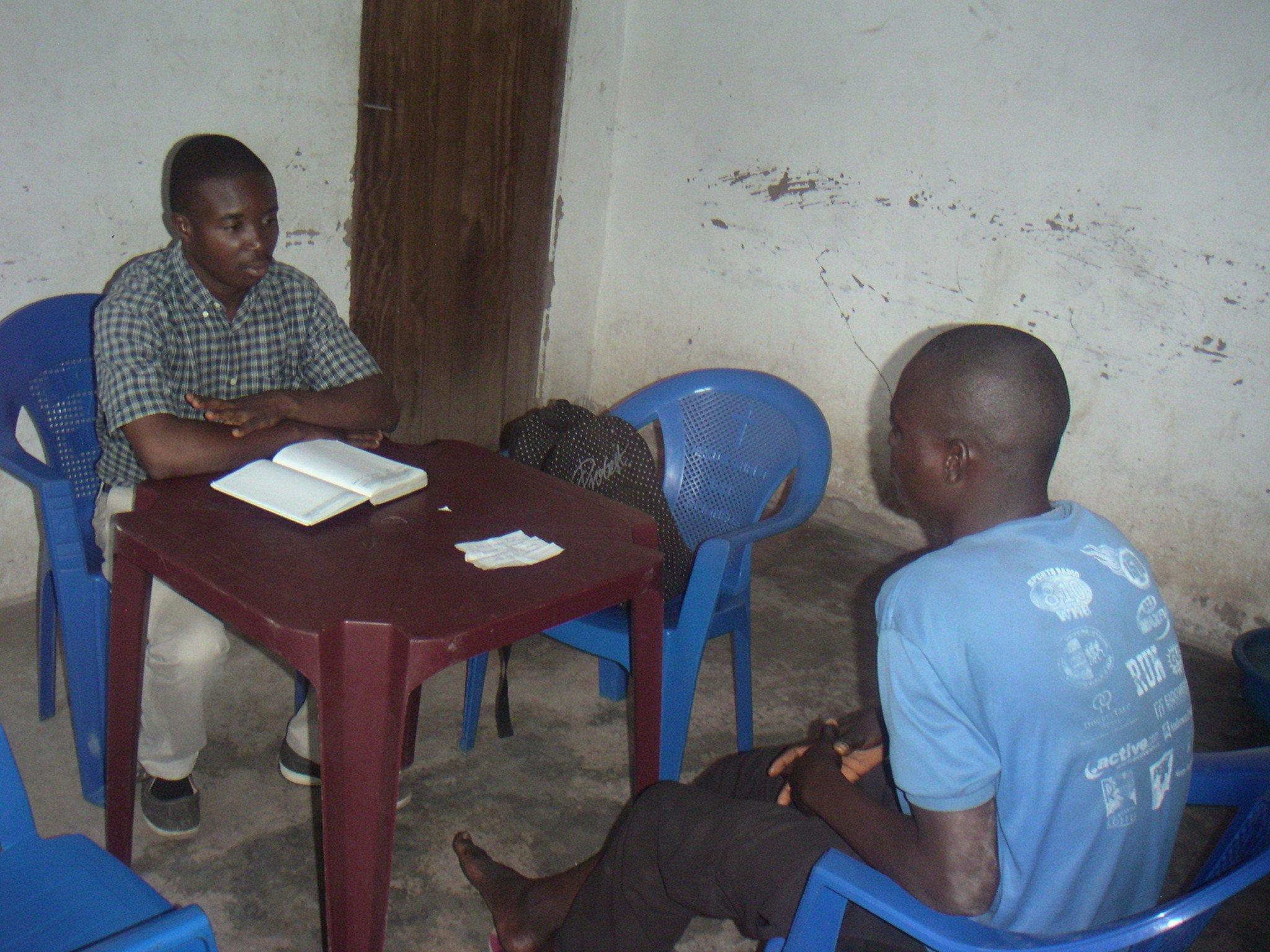 The volunteer Donatien is listening  to a prisoner